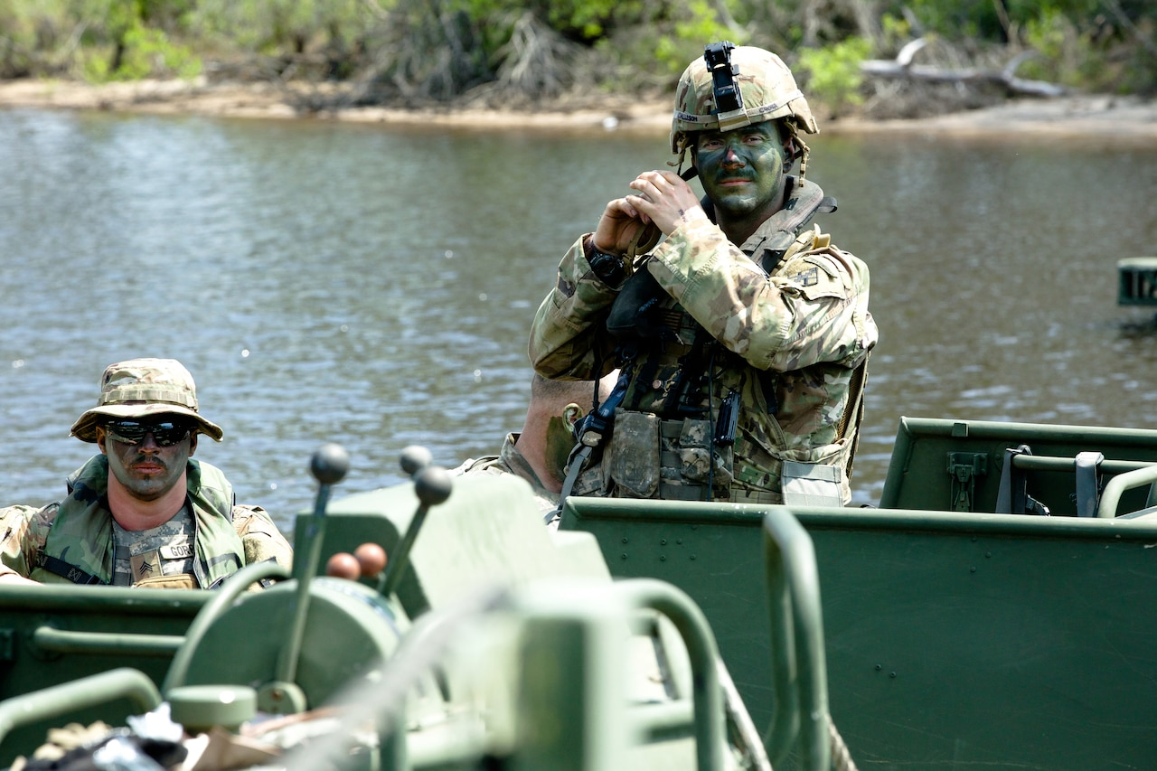 Two soldiers ride in small boat.