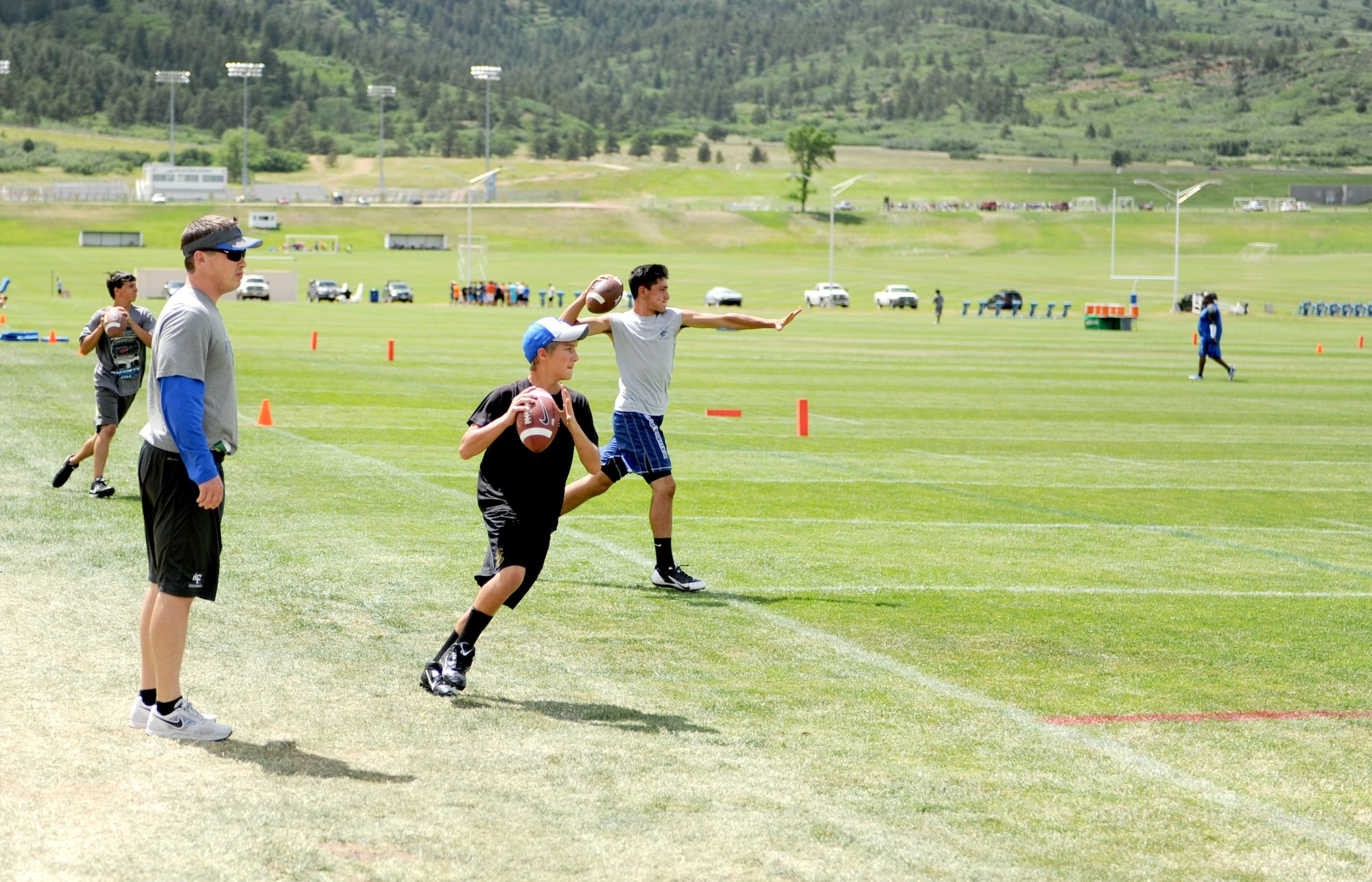 Youth sharpen their football skills during a youth football camp. Air Force Youth Programs is offering a variety of summer camps for 2019 to include more than 10 sports camps. (U.S. Air Force photo)