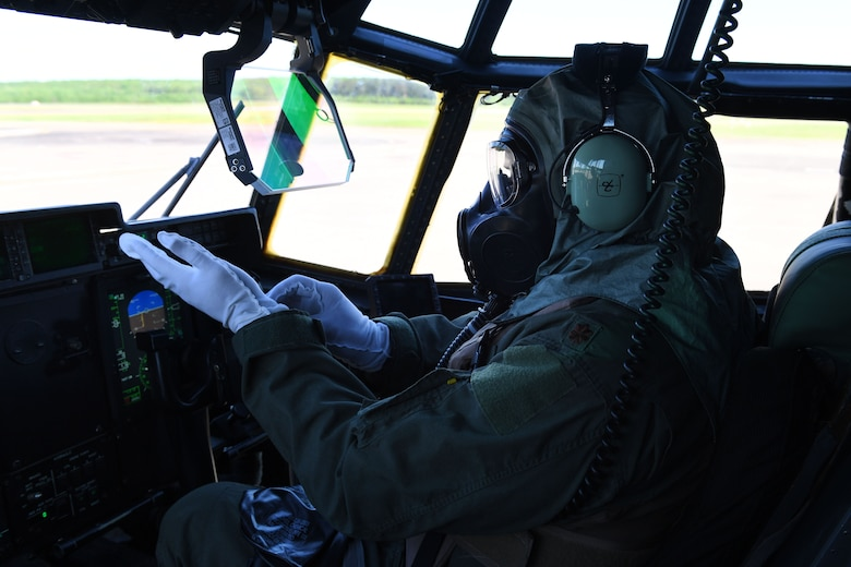 A pilot puts on gloves in the cock pit of a C-130J