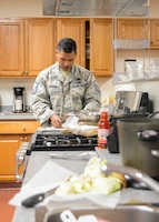 Master Sgt. David Garner, AFOTEC Det. 5, rolls a Filipino dish called lumpia during a cooking class as part of Asian American Pacific Islander Month at the Airmen and Family Readiness Center on Edwards Air Force Base, California, May 1. Other cooking classes are scheduled throughout the month to celebrate AAPI heritage. (U.S. Air Force photo by Giancarlo Casem)