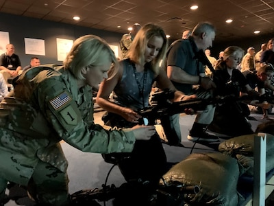 Mrs. Melissa Friez is the Assistant Superintendent of Student Support Services in the Pittsburgh public schools district. Col. Dina Wandler, Commander 1st Recruiting Brigade, shows Friez how to load an M4 rifle during a visit to the engagement skills trainer at the Army Educator Tour.