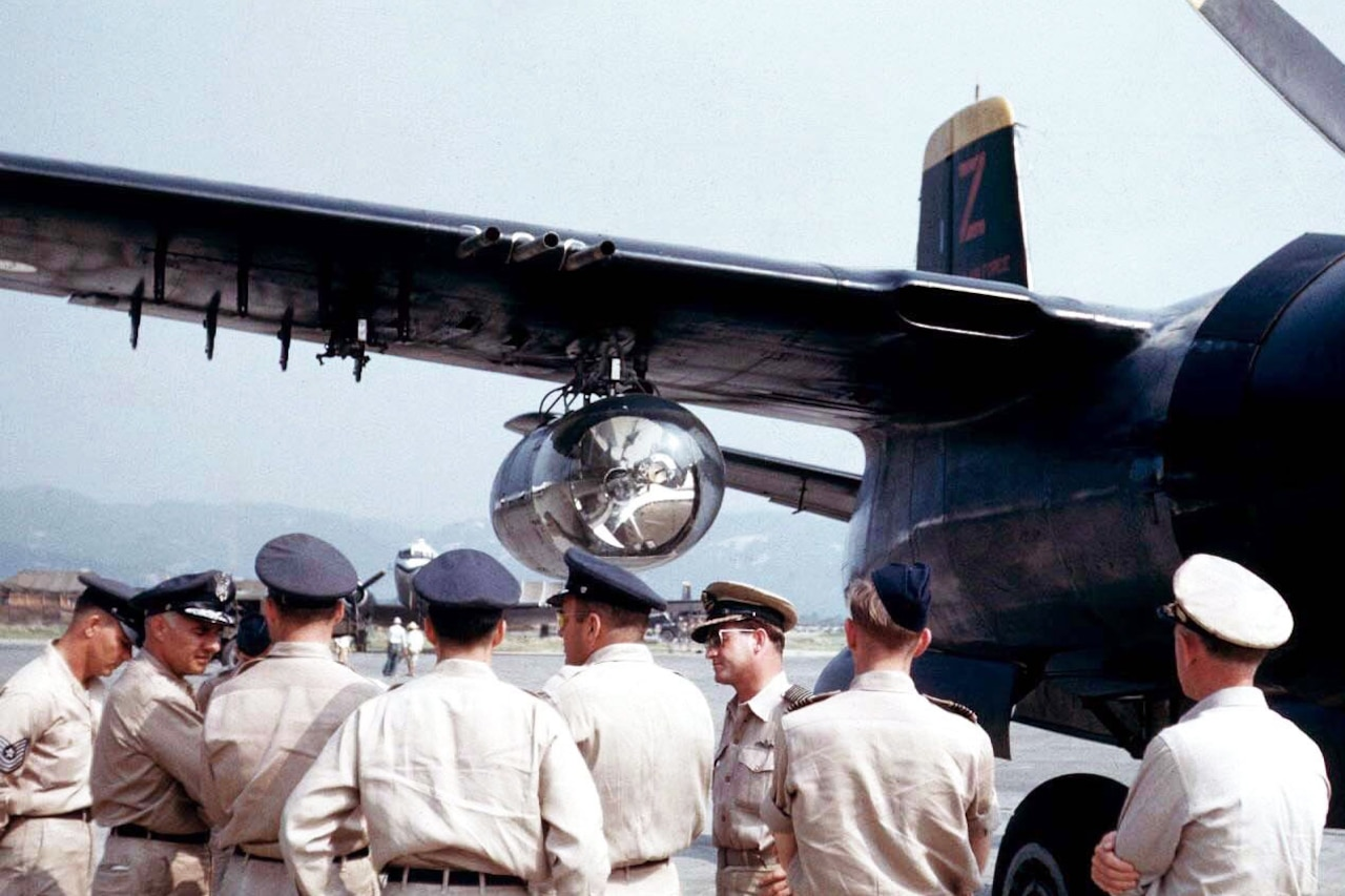 Eight uniformed service members stand beside the searchlight attached to a B-26 Invader.