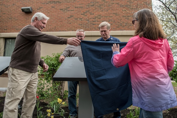Retired Kentucky Air National Guardsmen unveil a plaque bearing the names of 30 Airmen who retired from the 123rd Airlift Wing in 2018 during a ceremony at the Kentucky Air National Guard Base in Louisville, Ky., April 13, 2019. The annual unveiling commemorates Airmen who served for 20 or more years. (U.S. Air Force photo by Staff Sgt. Joshua Horton)