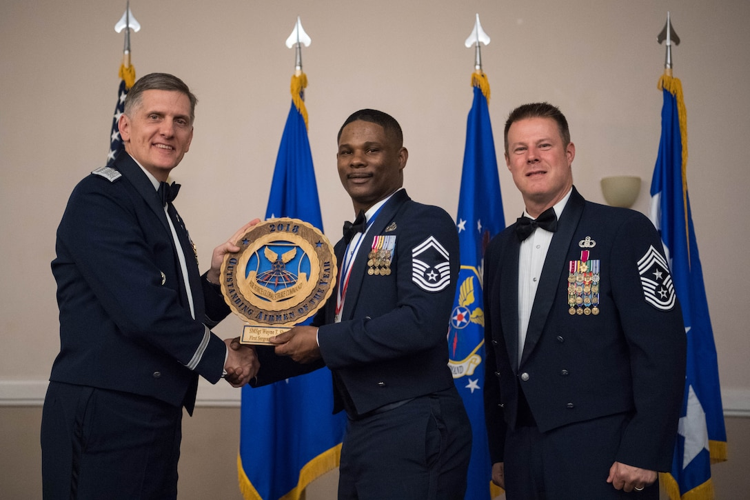 U.S. Air Force Senior Master Sgt. Wayne T. Sharp (middle), 5th Maintenance Squadron first sergeant at Minot Air Force Base, N.D., receives an Air Force Global Strike Command Outstanding Airmen of the Year award April 15, 2019, at Barksdale Air Force Base, La. The OAY award was awarded to six Airmen throughout AFGSC. (U.S. Air Force photo by Airman Jacob B. Wrightsman)