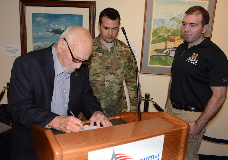 "Ramon Carpenter, a retired United States Naval aviator, signs the required paperwork after performing his grandson's commissioning oath. Master Sgt. David Barber, an officer accessions recruiter assigned to Dobbins Air Reserve Base, Georgia, served as  Garren ""Ridge"" Belflower's recruiter. The oath took place at the Museum of Aviation at Robins Air Force Base, Georgia. Belflower joins a long list of family members who have served in the United States military. (Air Force photo/Master Sgt. Chance Babin)"