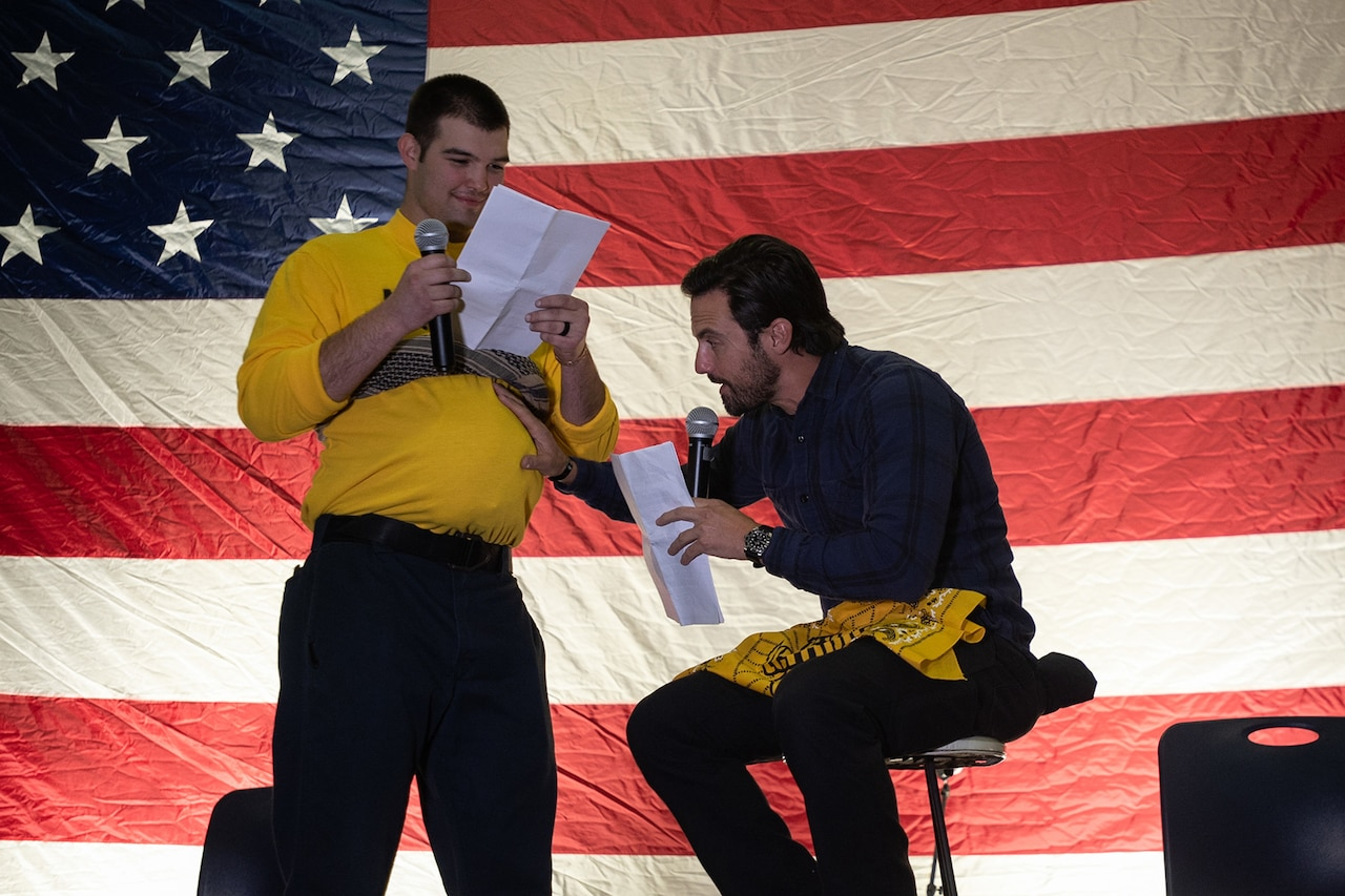 A man sits on a stool holding a microphone and the fake pregnant stomach of a man standing and reading from a script beside him. A U.S. flag is the backdrop.