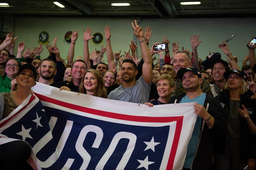 A group of people holding a USO banner raise their hands and give peace signs to a camera.