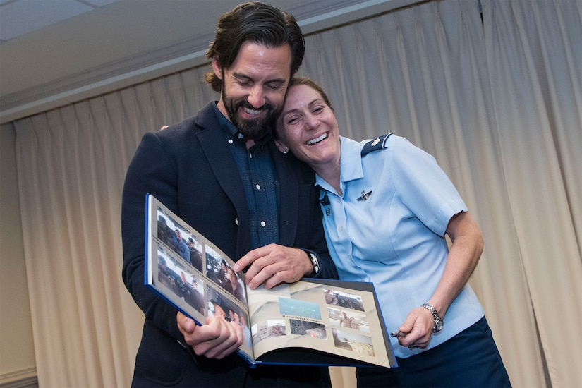A man holding a scrapbook laughs with a female airman, who is hugging the man from the side.