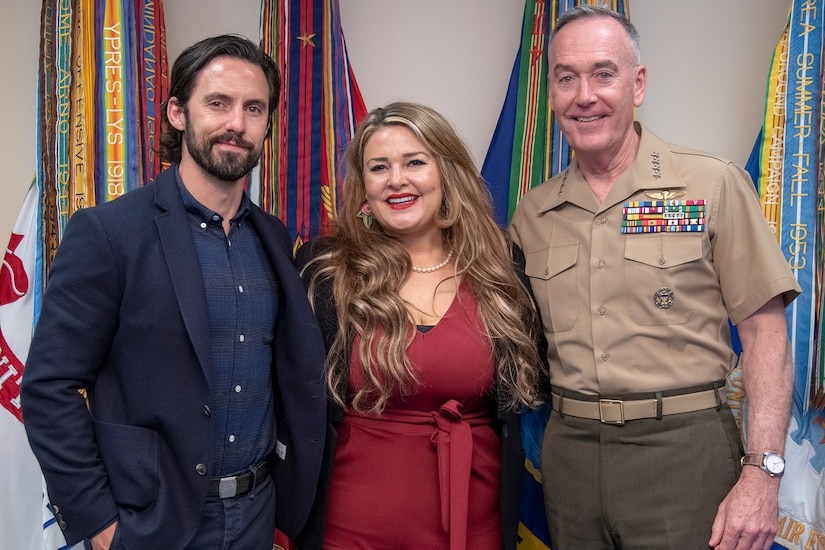 A man and a woman poses with a Marine Corps general in front of several flags.