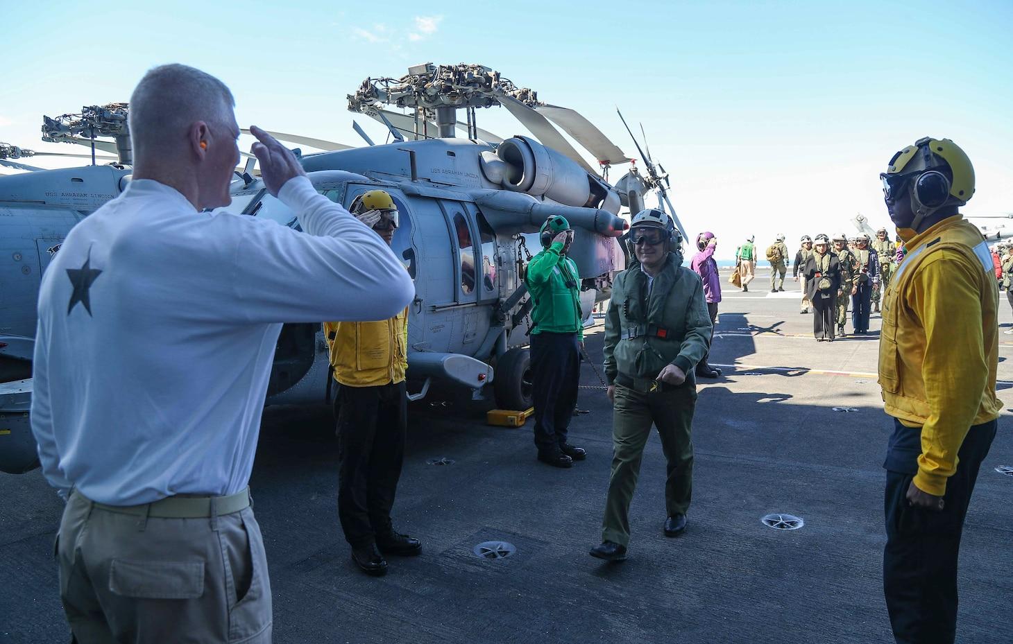 Rear Adm. John Wade, commander, Carrier Strike Group 12 (left), greets President Ilir Meta of Albania, on the flight deck of the Nimitz-class aircraft carrier USS Abraham Lincoln (CVN 72).