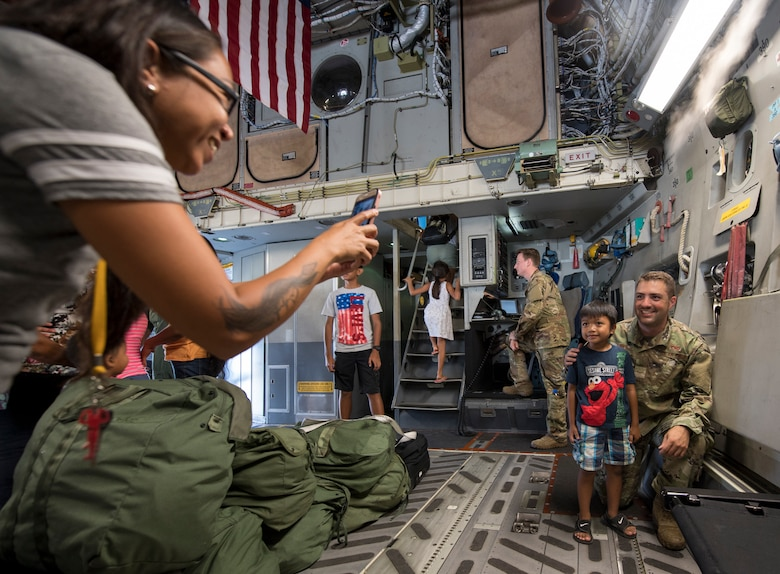 An Airman poses for a photo during a tour of a C-17 Globemaster III