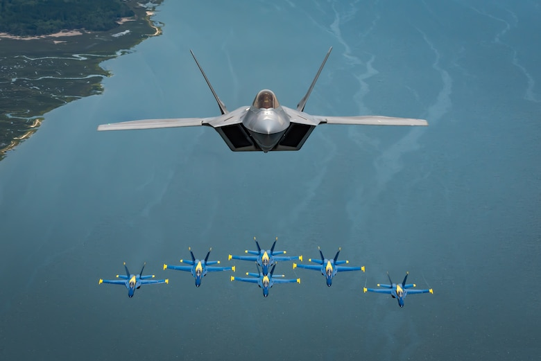 The F-22 Demo Team commander, flies above the U.S. Navy Blue Angels' iconic diamond formation