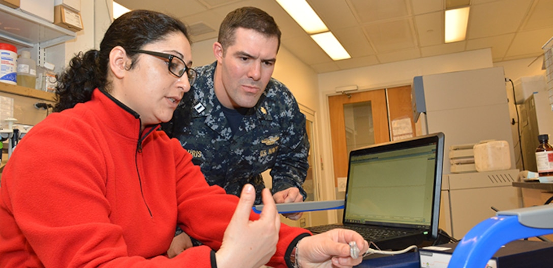 Researchers look at an electronic medical device.