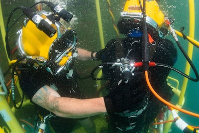 A diver adjusts the gas mix for another diver.