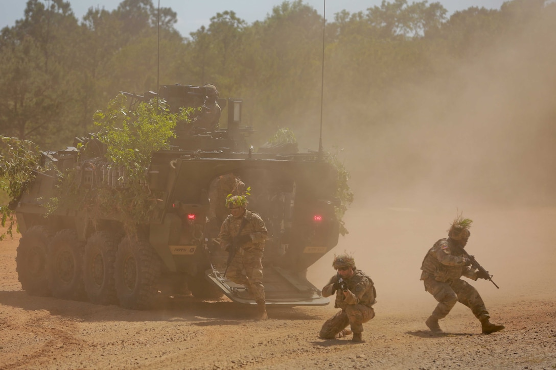 Soldiers stand and kneel around a military vehicle as dust swirls around them.