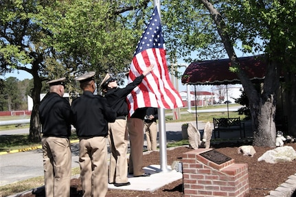 A United States Navy color guard carefully handles the American flag at the flag-raising ceremony at Joint Expeditionary Base Little Creek-Fort Story, Virginia, April 1, 2019, in honor of Master Chief Carl Brashear, who became the first African-American to attend and graduate from the U.S. Navy Diving & Salvage training school.  The site of the Official US Navy Chief Petty Officers Club is dedicated as a memorial to Brashear - the first African-American U.S. Navy diver - in honor of his strength, courage, determination, and the power of a can-do attitude and spirit.