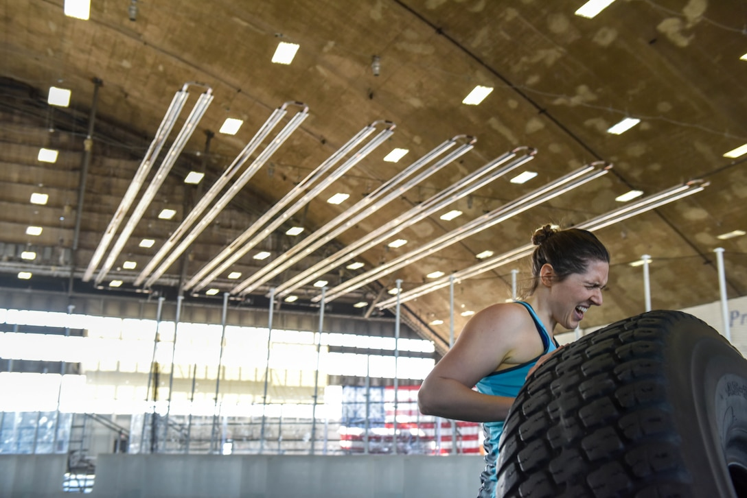 Eugene Weaver, a military spouse, flips a tire down the Pride Hangar's turf field during the Ellsworth Air Force Base's Strongest Competition on Ellsworth AFB, S.D., April 25, 2019. The free sporting event was hosted by the 28th Force Support Squadron. Competitors performed feats of strength throughout five different exercises: max-out deadlift, farmer's carry, keg run, tire flip and vehicle pull. Weaver placed third in the strongest female category. (U.S. Air Force photo by Tech. Sgt. Jette Carr)