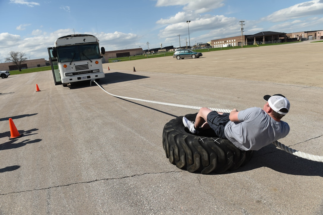 Senior Airman Wesley Tyner, 28th Logistics Readiness Squadron vehicle operations control center support, pulls a bus forward during the Ellsworth Air Force Base's Strongest Competition at the Pride Hangar parking lot on Ellsworth AFB, S.D., April 25, 2019. Tyner succeeded in his efforts, muscling the bus to the cones that signified the finish line for that event. The vehicle pull was one of five feats of strength used to determine who would go home with the title of strongest man or woman on base. Other areas of the competition included a max-out deadlift, farmer's carry, keg run and tire flip. (U.S. Air Force photo by Tech. Sgt. Jette Carr)