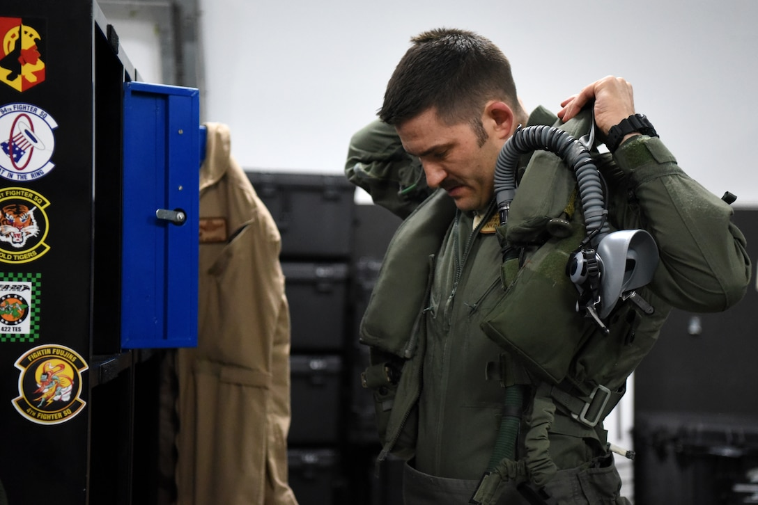An F-35A Lightning II pilot assigned to the 4th Expeditionary Fighter Squadron dons a sleeveless flight jacket in preparation for the first combat sortie in the U.S. Air Forces Central Command area of responsibility April 26, 2019, Al Dhafra Air Base, United Arab Emirates.