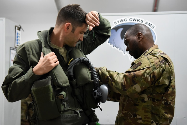 An F-35A Lightning II pilot assigned to the 4th Expeditionary Fighter Squadron receives assistance in securing gear to his sleeveless flight jacket in preparation for the first combat sortie in the U.S. Air Forces Central Command area of responsibility April 26, 2019, Al Dhafra Air Base, United Arab Emirates.