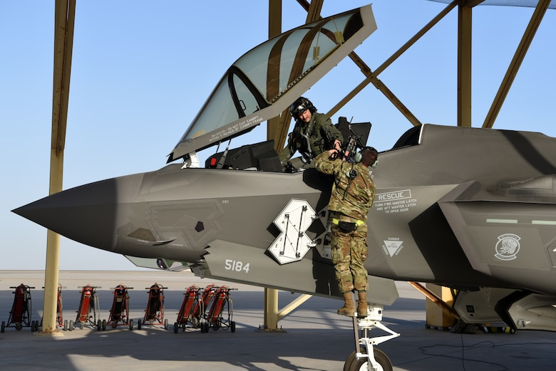 An F-35A Lightning II pilot assigned to the 4th Expeditionary Fighter Squadron passes gear to a 380th Expeditionary Aircraft Maintenance Squadron crew chief after running system checks on the aircraft April 26, 2019, Al Dhafra Air Base, United Arab Emirates.