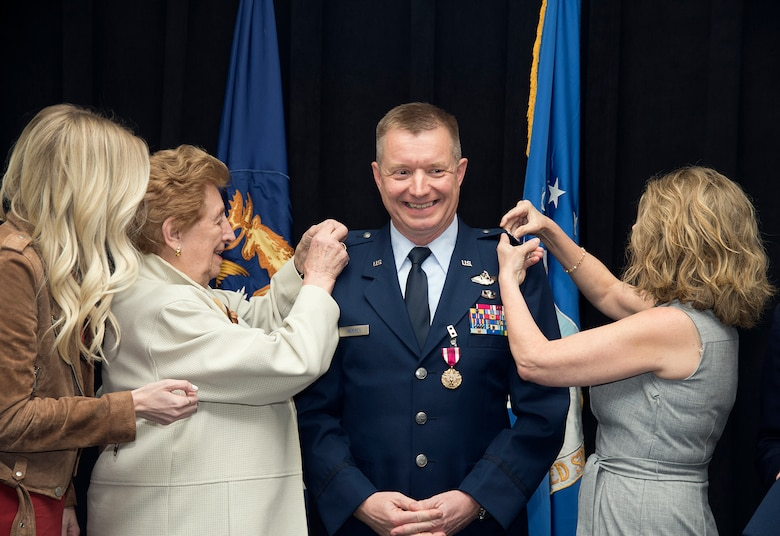 Brig. Gen. Rolf E. Mammen, commander of the 127th Wing and Selfridge Air National Guard Base, has his rank pinned on by his mother, Hannah and his wife, Linda as his daughter looks on during his promotion ceremony here, May 4, 2019.