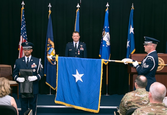Brig. Gen. Rolf E. Mammen, commander of the 127th Wing and Selfridge Air National Guard Base, stands as the general officer flag is ceremoniously unfurled during his promotion ceremony here, May 4, 2019.