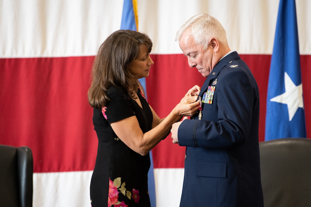 Terri Hayworth pins a retirement pin on Col. Douglas D. Hayworth, 137th Special Operations Wing (137th SOW) vice commander, during his retirement ceremony at Will Rogers Air National Guard Base in Oklahoma City, May 4, 2018. Hayworth retired after serving more than 30 years with the Wing. (U.S. Air National Guard photo by Senior Airman Jordan Martin)