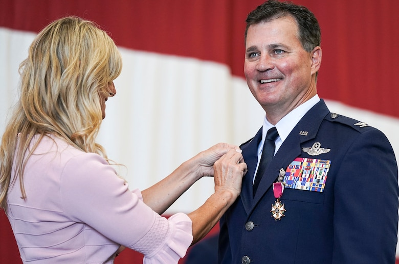 Col. Devin R. Wooden, former 137th Special Operations Wing commander, receives a retirement pin from his wife, Kelly Wooden, during his retirement ceremony at Will Rogers Air National Guard Base, May 5, 2019. Wooden spent his entire career, nearly 33 years, promoting from Airman 1st Class to Colonel in the Oklahoma Air National Guard. (U.S. Air National Guard photo by Staff Sgt. Tyler Woodward)