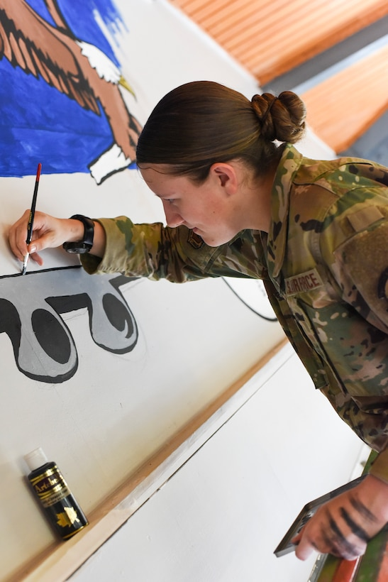 Airman First Class Amber Branch, 728th Air Mobility Squadron passenger services agent, paints a C-5 Galaxy on a mural in the squadron's heritage room Feb. 1, 2019, at Incirlik Air Base, Turkey. Branch began drawing as a child and her love for it developed into creating paintings. (U.S. Air Force photo by Staff Sgt. Ceaira Tinsley)