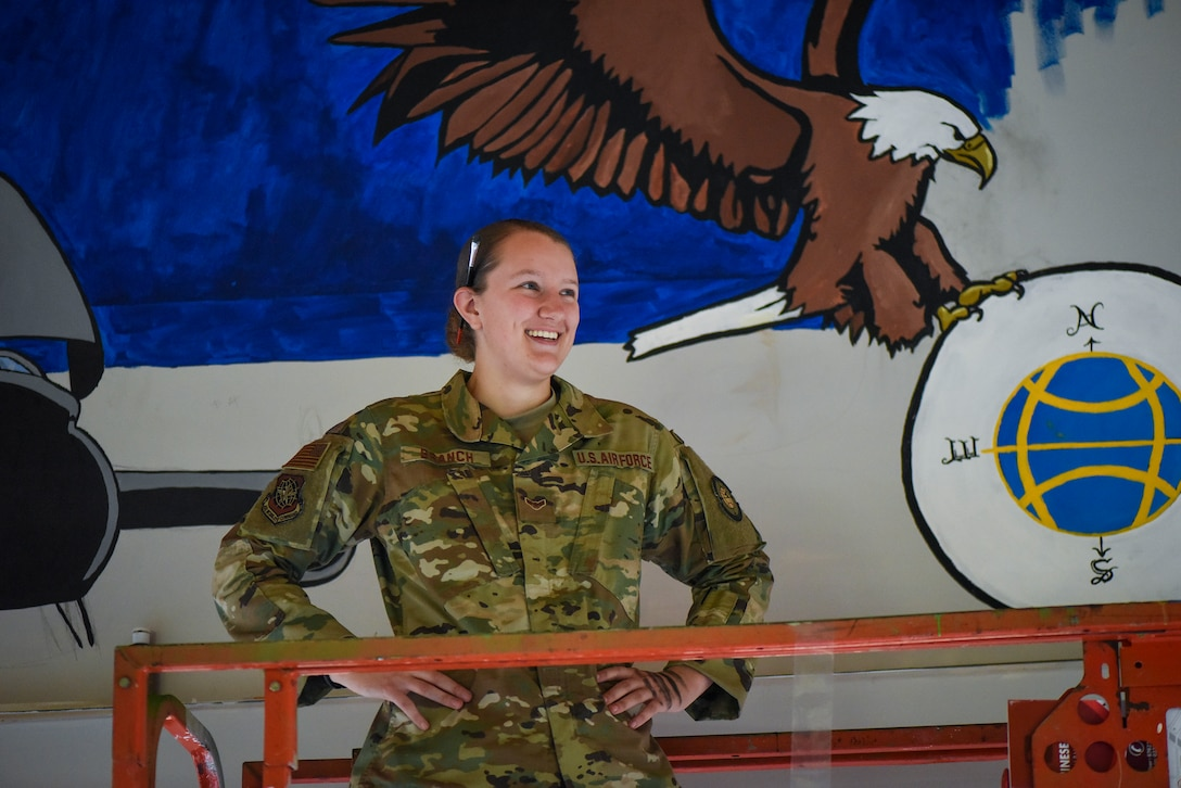 Airman First Class Amber Branch, 728th Air Mobility Squadron passenger services agent, poses for a photo in front of a mural in the squadron's heritage room Feb. 1, 2019, at Incirlik Air Base, Turkey. Branch used the mural as an opportunity to combine her love for her job with her love for drawing. (U.S. Air Force photo by Staff Sgt. Ceaira Tinsley)