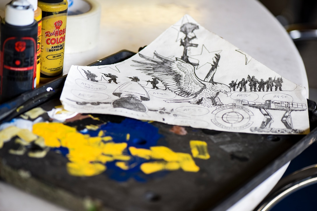 A drawing and paint supplies rest on a table in the 728th Aircraft Mobility Squadron's heritage room Feb. 1, 2019, at Incirlik Air Base, Turkey. The 728th AMS selected Airman First Class Amber Branch, 728th AMS passenger services agent, to create a mural encompassing the unit's mission. (U.S. Air Force photo by Staff Sgt. Ceaira Tinsley)