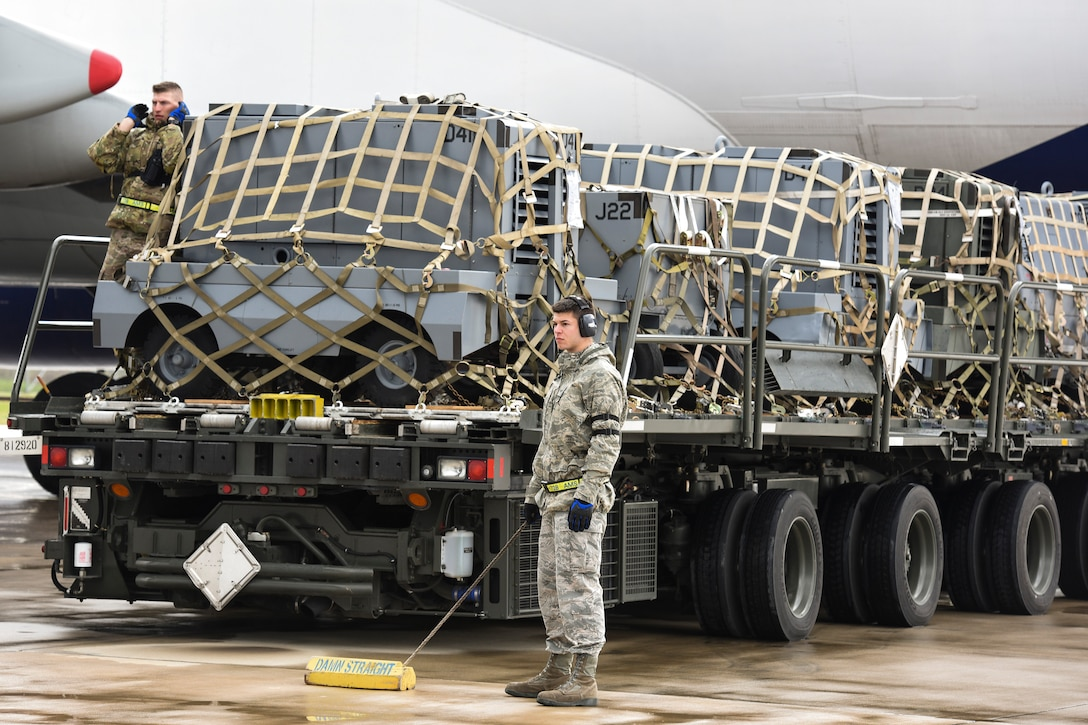 Staff Sgt. Daniel Lauritzen, 728th Air Mobility Squadron aircraft services supervisor, and Senior Airman Dane Johnson, 728th AMS aircraft services journeyman, direct a K-Loader into place March 3, 2019, at Incirlik Air Base, Turkey. Airmen in the 728th AMS use K-loaders to offload and download thousands of pounds of cargo weekly. (U.S. Air Force photo by Staff Sgt. Ceaira Tinsley)