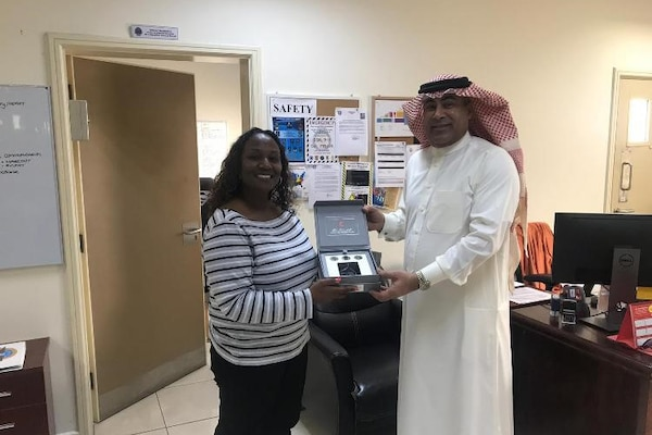 Shireen Washington, a disposition service representative for DLA Disposition Services in Bahrain, accepts replicas of historic items from Mohammed Ebrahim, a supervisor from the local Red Crescent Society, offered in appreciation for the furniture and other items provided to help the charity serve those in need.