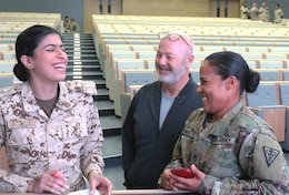 1st Lt. Maryam Abdulla, a doctor in the Bahrain Defence Force, and U.S. Army Sgt. 1st Class Misbah Bailey, 8th Medical Brigade, share a laugh while preparing a nine line at the Crown Prince Center of Training and Medical Research in Bahrain, April 16, 2019.