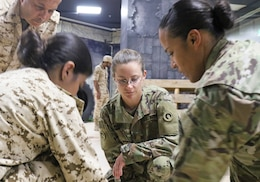 U.S. Army Maj. Tosha Nichols, 1st Theater Sustainment Command, watches as a tourniquet is applied during a medical subject matter expert exchange at the Crown Prince Center of Training and Medical Research in Bahrain, April 15, 2019.