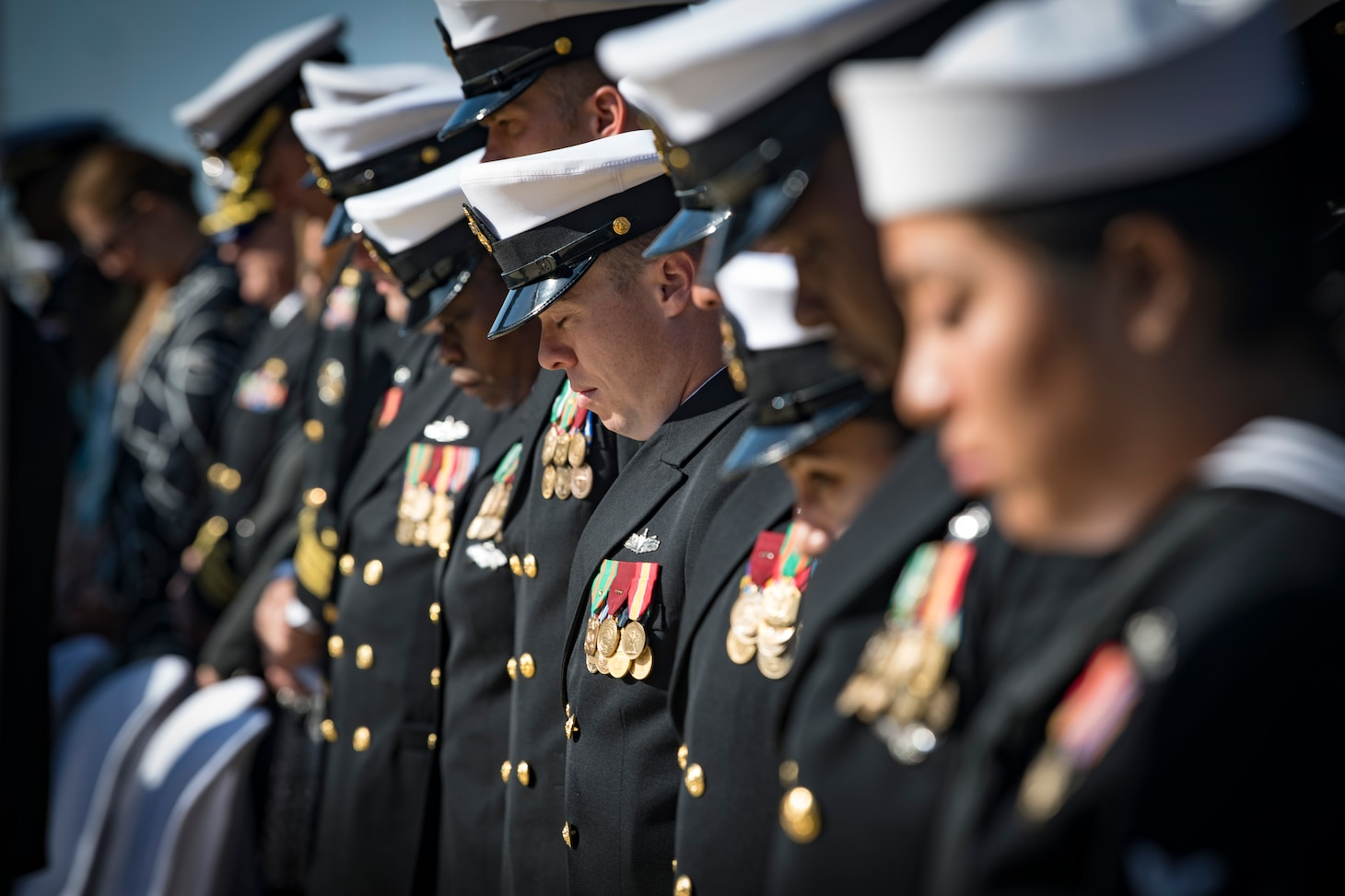The official party from the Arleigh Burke-class guided-missile destroyer USS Donald Cook (DDG 75) salute as the color guard parades the colors during a change of command ceremony for the ship, May 3, 2019.
