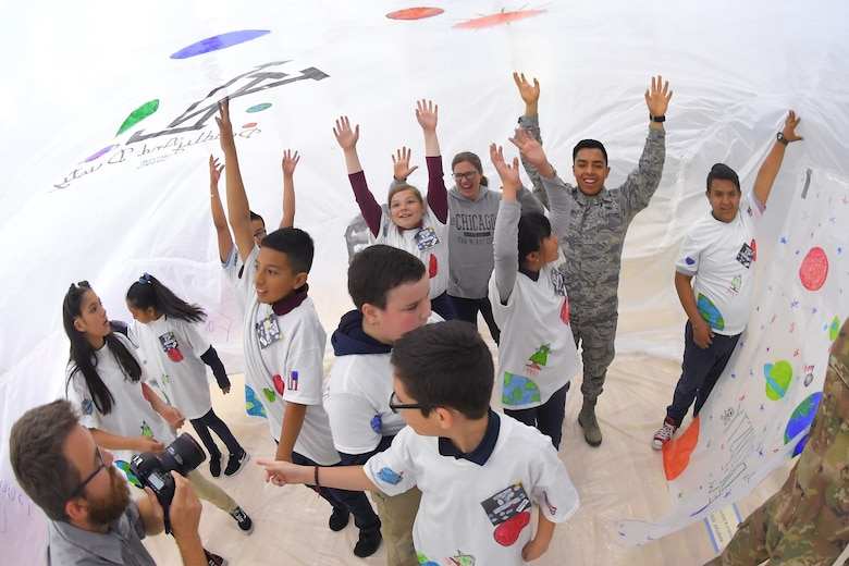 Airman 1st Class Kenny Dela Cruz, 75th Comptroller Squadron, and fifth grade school children during the building of a simulated space habitat called 'Mission to Mars' at Weber State University May 2, 2019. Mission to Mars is facilitated by Hill Air Force Base as part of the STEM Outreach Program, which partners with local school teachers by providing a curriculum, materials and events to teach STEM-related subjects in a creative and fun environment. (U.S. Air Force photo by Todd Cromar)