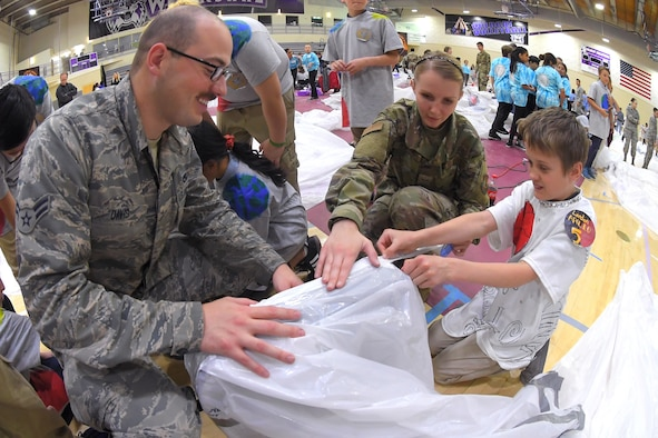 (Left to right) Airman 1st Class Zack Davis and Senior Airman Ashley Carey, both 649th Munitions Squadron, assist a fifth grade student with building a simulated space habitat during 'Mission to Mars' at Weber State University May 2, 2019. Mission to Mars is facilitated by Hill Air Force Base as part of the STEM Outreach Program, which partners with local school teachers by providing a curriculum, materials and events to teach STEM-related subjects in a creative and fun environment. (U.S. Air Force photo by Todd Cromar)
