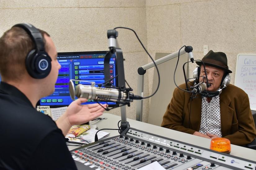 Two men speak into microphones in a radio studio.