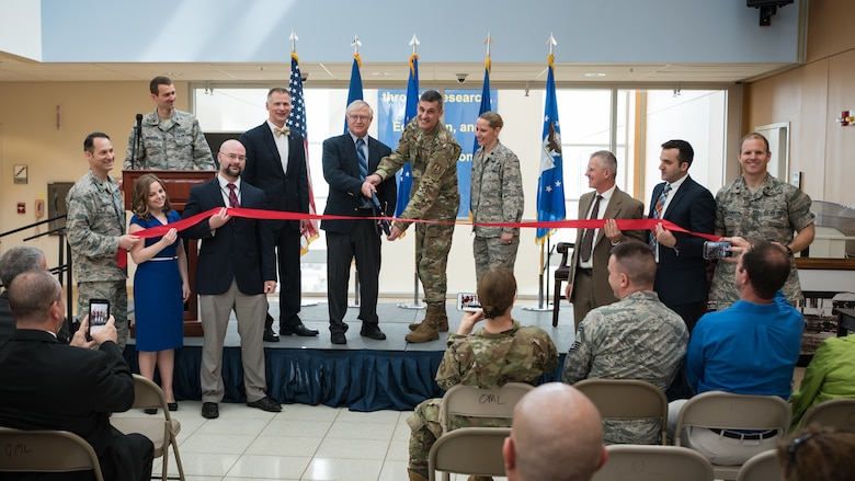 Jack Blackhurst, executive director of the Air Force Research Laboratory, and Brig. Gen. Mark Koeniger, commander of the 711th Human Performance Wing, prepare to cut a ceremonial red ribbon in honor of the activation of the Warfighter Medical Optimization Division, one of five divisions comprising the 711HPW's Airman Systems Directorate. The activation ceremony was held May 1 at the United States Air Force School of Aerospace Medicine. (U.S. Air Force photo/Rick Eldridge)