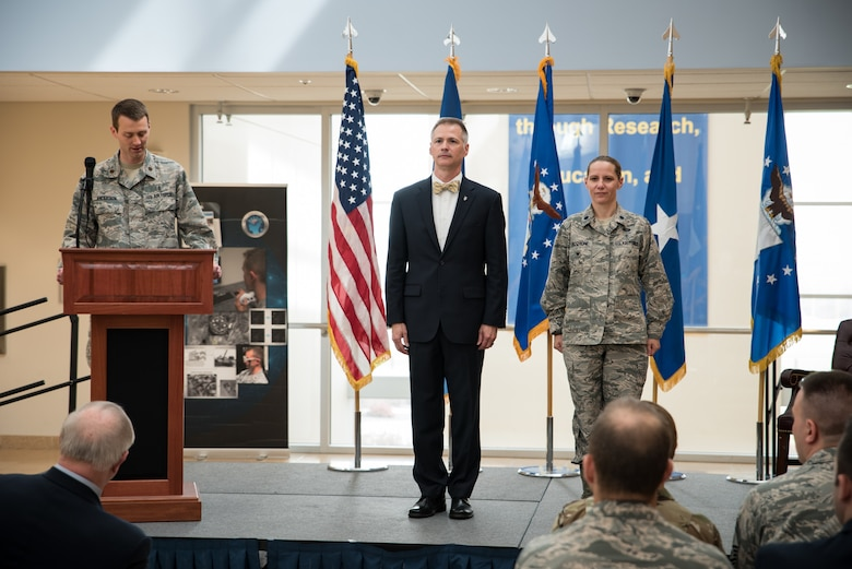 Dr. Kevin Geiss, director of the 711th Human Performance Wing's Airman Systems Directorate, and Lt. Col. Jennifer Vecchione, chief of the newly established Warfighter Medical Optimization Division stand during the reading of the charter activation document at a ceremonial ribbon cutting ceremony in honor of the activation of the Warfighter Medical Optimization Division, one of five divisions comprising the Airman Syustems Directorate. The activation ceremony was held May 1 at the United States Air Force School of Aerospace Medicine. (U.S. Air Force photo/Rick Eldridge)