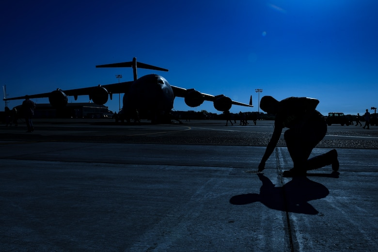 Tech. Sgt. Jason Fish, repair and reclamation/wheel and tire technician with the 911th Maintenance Group, picks up a piece of foreign object debris during a FOD walk at Pittsburgh International Airport Air Reserve Station, Pennsylvania, May 6, 2019. Performing FOD walks ensures the flightline is clear of any loose objects that could get sucked into and destroy an aircraft engine.