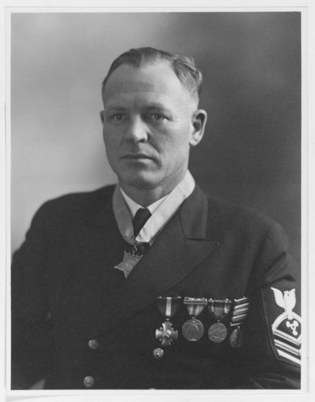 A sailor in uniform wears the Medal of Honor and four other medals.