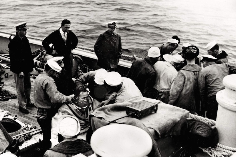 Three men help a diver put his gear on as other men huddle around.