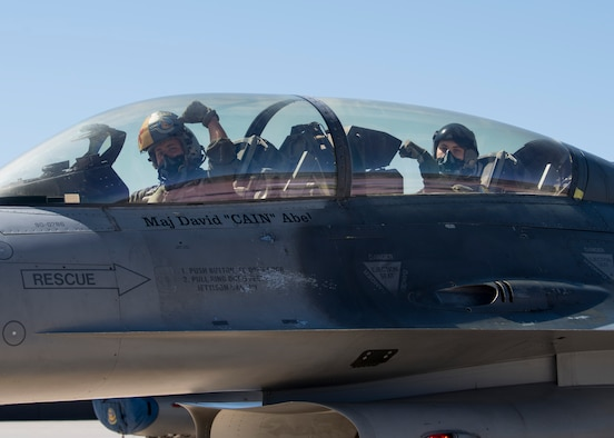"Maj. David Abel, 311th Fighter Squadron instructor pilot, left, and 2nd Lt. Sean Stegmoller, 54th Operations Support Squadron intelligence officer, right, display the 311th Fighter Squadron's ""Fangs Out"" symbol during a familiarization flight, May 2, 2019, on Hill Air Force Base, Utah. Abel was assigned to the 311th FS for his F-16 Basic Course, and graduated from the 311th FS a second time after completing the instructor pilot course. (U.S. Air Force photo by Staff Sgt. BreeAnn Sachs)"