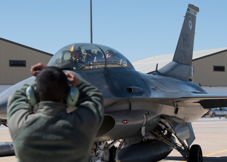 Senior Airman Dennis Labayen, 311th Aircraft Maintenance Unit Dedicated Crew Chief, signals Maj. David Abel, 311th Fighter Squadron instructor pilot, to park, May 2, 2019, on Hill Air Force Base, Utah. Abel flew the final sortie of his instructor pilot upgrade training, April 23, 2019, the first day of exercise Venom 19-01, and flew 2nd Lt. Sean Stegemoller, 54th Operation Support Squadron intelligence officer, in his first familiarization flight the last day of the exercise. (U.S. Air Force photo by Staff Sgt. BreeAnn Sachs)