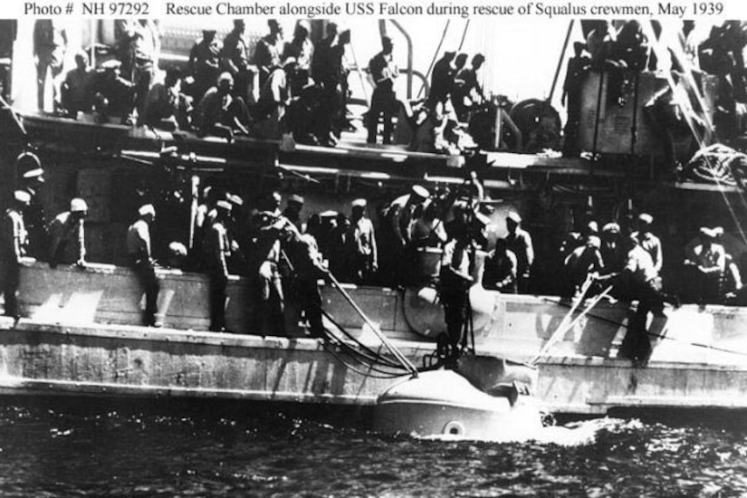 A boat beside a larger vessel surrounded by men pulls in the top of a rescue chamber.