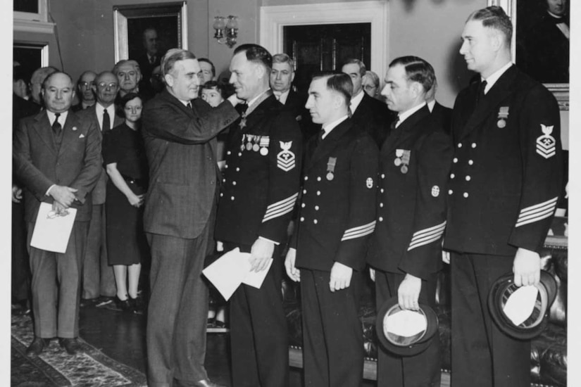 Four sailors in dress blues stand in line to receive the Medal of Honor from a man in a suit as others look on.