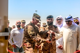 U.S. Army Col. Guy Reedy, 1st Theater Sustainment Command's Operational Command Post chief of staff,  Kuwait Col. Abdullah Hamed Al-Masamah,  Khabari Crossing operations manager, and Jamal Al-Julawi, director general of customs administration, cut the ribbon on a newly rennovated facility at Khabari Crossing, Kuwait, April 30, 2019.
